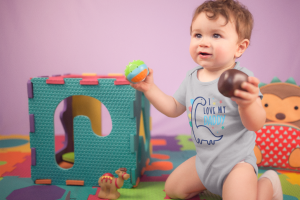 pretty-baby-boy-playing-with-toys-wearing-a-onesie-while-on-his-knees-at-his-playground-mockup-a14023
